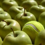 A single tennisball in a bunch of apples.
